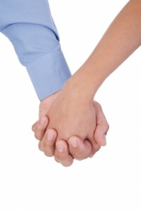 Closeup Of Young Affectionate Couple Holding Hands Over White Ba by David Castillo Dominici